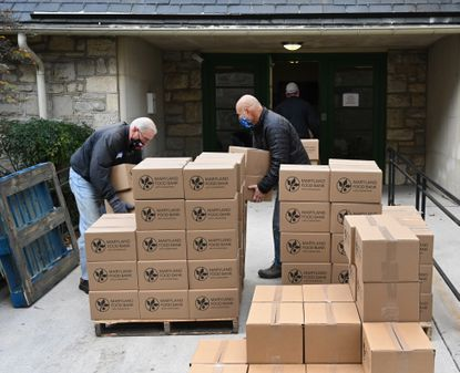 Gus Bengel, left, and Ted Root, right, work to move the last of the Maryland Food Bank boxes inside as they and other volunteers come together at the Assistance Center of Towson Churches at the Trinity Episcopal Church in Towson on Nov. 18 to prepare hundreds of food bags for the group's annual Thanksgiving deliveries.