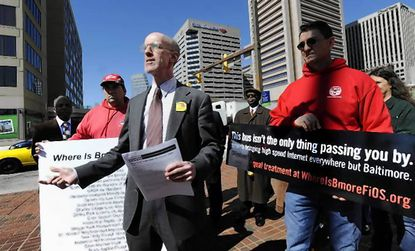 Matthew Weinstein, of Progressive Maryland, launches a bus billboard advertising campaign in March 2010 to pressure Verizon to bring high-speed fiber optic service ( FiOS) to the city. At right, a supporter holds a sign that's on 50 buses. The building at far left is Verizon.
