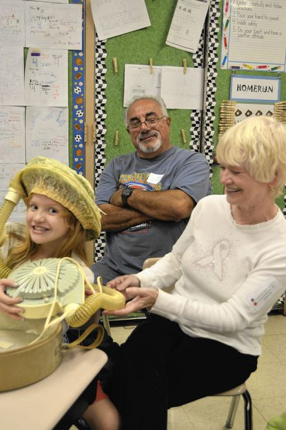 Third grader Stella Hamilton tries on an old-fashioned hairdryer for size with grandparents Mary and Dino Blazakis.