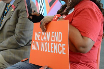 """Attendants of a 2019 roundtable discussion with U.S. Rep. Eric Swalwell in West Baltimore hold signs that read, """"We can end gun violence."""" (Hallie Miller/Baltimore Sun)."""