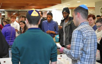 "Jewish and Islamic students take part in a Kiddish, a celebratory meal in the Jewish faith. About 50 Jewish and Islamic students from Hillel and the Muslim Students Association will convene to view ""Vision of Place, "" an exhibition of Israeli art, together."