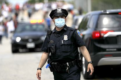A Baltimore police officer wears a mask while patrolling outside of Fort McHenry National Monument and Historic Shrine last year. (AP Photo/Julio Cortez)