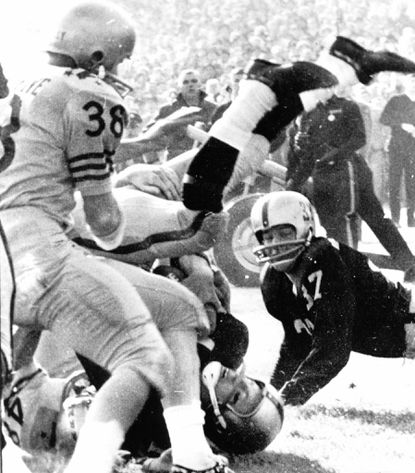 Army quarterback Rollie Stichweh winds up head down and feet up but with the ball tucked securely in his grasp for a score in the 1963 game against Navy.