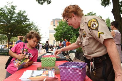 DFC Sue Thompson with the Baltimore County Sheriff's Office helps 9-year-old Dylan Mitchell-Strong to some freebies and its vendor table during the National Night Out event in Towson on Tuesday, Aug. 7.