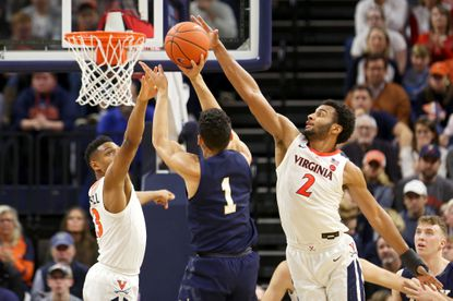 Casey Morsell, left, and Braxton Key of the Virginia Cavaliers block a shot by John Carter Jr. of the Navy Midshipmen in the second half during a game at John Paul Jones Arena on December 29, 2019 in Charlottesville, Virginia.