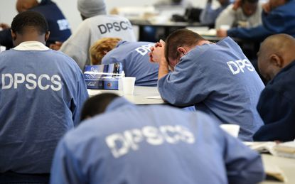 Inmates pray during a Christmas worship service at Dorsey Run Correctional Facility in 2017.