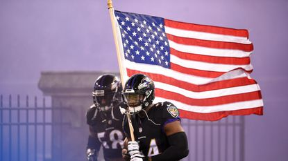 Ravens linebacker Tyus Bowser carries an American flag onto the field before the game against the Houston Texans on Nov. 27.