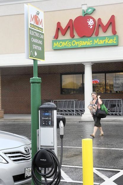 Jennifer DeVille, of Towson, walks with her son Beckett, four months, near an electric car charging station outside Mom's Organic Market on Aug. 1, in Timonium.