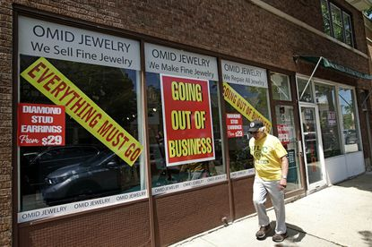 A man walks past a retail store that is going out of business due to the coronavirus pandemic in Winnetka, Ill., Tuesday, June 23, 2020. High unemployment rates have been offset, at least to a degree, by higher unemployment benefits, some of which are due to expire as early as July 31, however. (AP Photo/Nam Y. Huh)