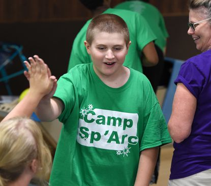 Camper Lenny Elliott gets a few big high fives as he returns to his seat after getting a strike as he and others with Camp Sp'Arc enjoy some fun Wednesday afternoon at Harford Lanes in Aberdeen.