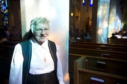 Sister Dolora Taylor is illuminated by sunlight shining through stained glass windows at Immaculate Conception Church in Towson.