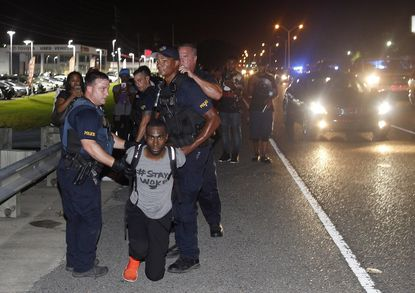 Police arrest activist DeRay Mckesson during a protest along Airline Highway, a major road that passes in front of the Baton Rouge Police Department headquarters Saturday, July 9, 2016, in Baton Rouge, Louisiana. The 5th U.S. Circuit Court of Appeals has ruled a police officer can sue Mr. Mckesson for injuries he suffered during the protest.
