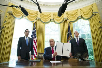 President Donald Trump holds up a signed executive order to increase sanctions on Iran in the Oval Office on June 24, 2019.