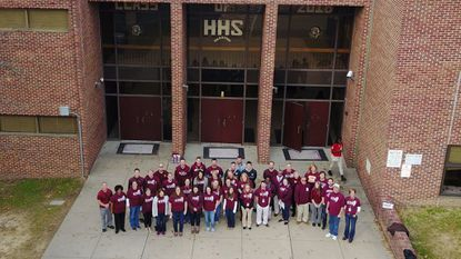 Havre de Grace High School staff stand outside the school on Maroon Monday, wearing their school colors in anticipation that the Harford County Board of Education would approve contracts that evening to build a new school.