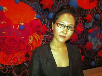 """Mina Cheon in front of her 72 x 8 feet painting """"15 Billion Years of the Traveling Atom,"""" currently on view at Maryland Art Place"""
