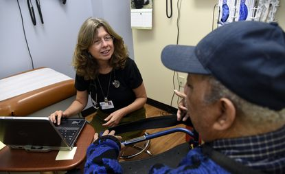 Dr. Kari Alperovitz-Bichell, left, talks with patient Preston Holland, a resident of Morris Blum Senior Apartments, as he visits the Anne Arundel Medical Center community clinic that is located on the ground floor of his building.