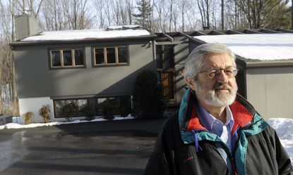 Glen Arm, MD--Feb. 20, 2014--Ben Benokraitis stands in front of his home, which has two solar panels on the roof.