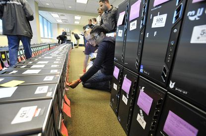 Andrew Murray, Lutherville, and Karel Charles, Lutherville, look at computer towers to be sold at the Big Huge Games auction.