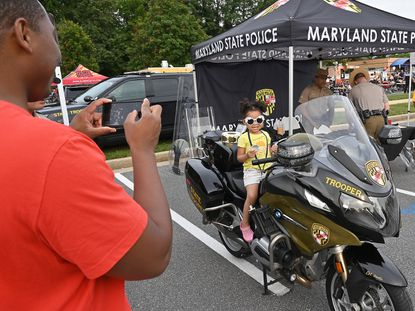 Roger Montgomery takes a photo of his daughter, Luna, 3, on a Maryland State Trooper motorcycle at National Night Out at East Columbia Library in Owen Brown, Columbia, August 3, 2021.