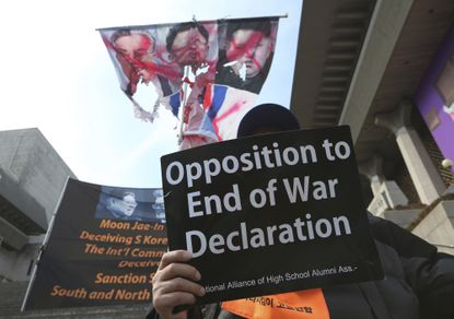 A South Korean protester holds a card during a rally to oppose end of the Korean War declaration in the upcoming summit between U.S. President Donald Trump and North Korean leader Kim Jong Un near the U.S. embassy in Seoul, South Korea, Tuesday, Feb. 26, 2019. Kim's armored limousine, surrounded by his phalanx of burly bodyguards, rolled into Vietnam's capital Tuesday ahead of summit with Trump that's meant to deal with perhaps the world's biggest security challenge: His pursuit of a nuclear program that stands on the verge of viably threatening any target on the planet.