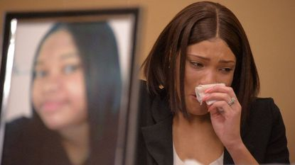 "Rosslyn Hall-Taylor fights her emotions behind her sister's photo during a press conference to address a ""patient dumping"" incident that left her sister in hospital gown on a cold night in downtown Baltimore in January."