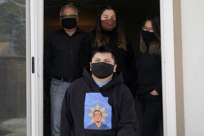 Andrei Quinto, foreground, wears a shirt with an image of his brother, Angelo Quinto, while posing for photos with Robert Collins, from top left, Bella Collins and Cassandra Quinto-Collins during an interview in Antioch, California on March 16, 2021. Angelo Quinto died three days after being restrained on Dec. 23, 2020, in police custody while having a mental health crisis. (AP Photo/Jeff Chiu)