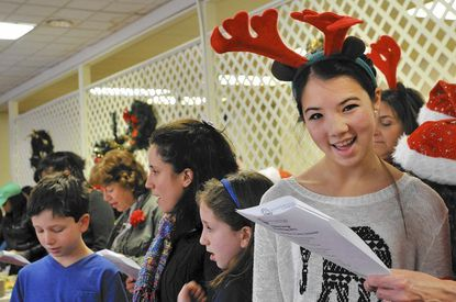 Cara Chen, right, came to Harmony Hall Assisted Living center in Columbia with her family as volunteers from The Jewish Federation of Howard County to sing and visit with seniors during their midday Christmas meal.