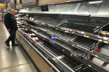 A shopper looks over empty refrigerated shelves in a meat section at a Walmart in Warrington, Pa., on Tuesday, March 17, 2020. Coronavirus concerns have led to consumer panic buying of grocery staples. (AP Photo/Matt Rourke)