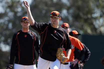 Orioles pitcher Chris Tillman, center, participates in a drill during the first spring training baseball workout for Orioles pitchers and catchers in Sarasota, Fla..