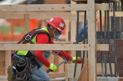 A construction worker wears a mask while working on the Towson Row site last week in the Baltimore County seat of government. On July 1, developers of such projects face impact fees that at least one county council member would like to delay.