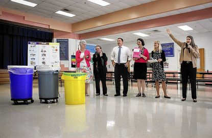 Howard County Public Schools Superintendent Renee Foose, far right, shows off a new yellow food scrap recycling bin at Pointers Run Elementary School.