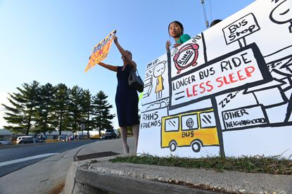 Alice Chen 12, center, who can see River Hill High from her backyard, might be redistricted out of the high school. She made the signs she and mother Fen Han are holding in protest. Anti-redistricting plan parents and students demonstrate at Howard County School Board headquarters.