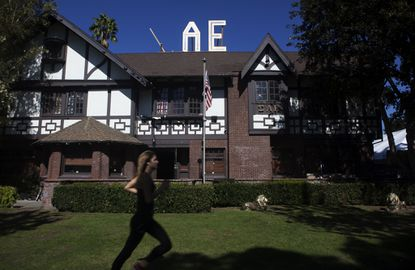 """A USC student runs in front of the Sigma Alpha Epsilon house in October 2013 on the university's """"fraternity row."""" The fraternity has been put on probation after a student from another college fell from a table during a party and was taken to the hospital."""