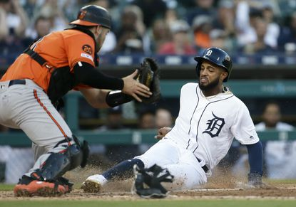 Willi Castroof the Detroit Tigers beats the tag from catcher Austin Wynns of the Baltimore Orioles to score on a single by Victor Reyes during the fifth inning at Comerica Park.