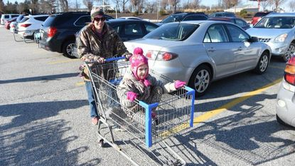 April Alexander of Whiteford pushes her daughter Sara in a shopping cart as they get ready to shop for holiday deals at the Walmart in Fallston on Tuesday, Dec. 26.