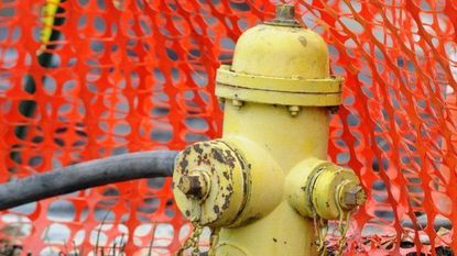 A hose is connected to a fire hydrant to help douse hotspots after a fire in Perryville.