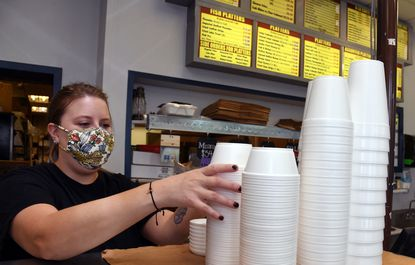 Rachel Schuman stacks foam containers on the front counter at Captain Dan's Crab House in Eldersburg, where employees are trying to use up the last of their containers before a new law that bans them takes effect Oct. 1.
