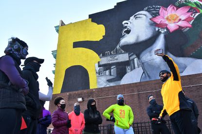 Rob Jackson, right, founder of the running group RIOT Squad (Running Is Our Therapy) shares Black history at Penn North, in front of a Billie Holiday mural at the Arch Social Club, during a chilly morning run. The RIOT Squad has incorporated Black history in their February runs. Feb. 21, 2021 p1