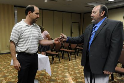 Shawn Quinn, Libertarian party gubernatorial candidate, introduces himself to Larry Manross, left, chairman of Baltimore County's Chapter of the Campaign for Liberty, during a recent meeting.