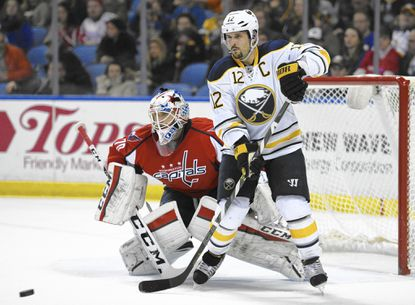 Washington Capitals goaltender Braden Holtby (70) watches an incoming shot along with Buffalo Sabres right winger Brian Gionta (12) during the first period of an NHL hockey game, Saturday, Jan. 16, 2016 in Buffalo, N.Y. (AP Photo/Gary Wiepert)