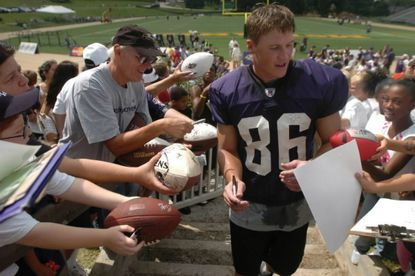 On the first day of Ravens training camp at McDaniel College in 2004, fans clamor for Todd Heap's autograph after the morning practice session.