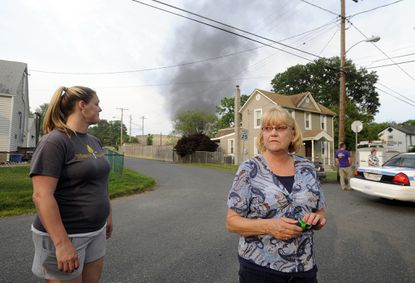 Kelly Gray, left, and Delores O'Neil, residents of Maryland Manor, look around their neighborhood after a train derailment and explosion nearby.