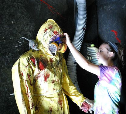 Katie Reightler, 17, adjusts the biohazard suit on a zombie mannequin in the Lineboro fire company's House of Horrors on Sept. 22. The zombie will be one of many scary attractions at Bedlam in the Boro beginning in October.