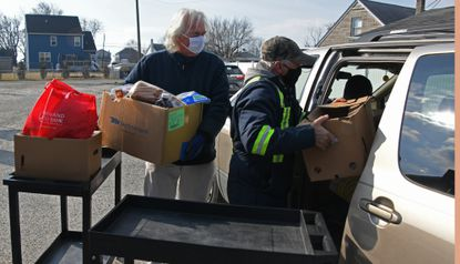 From left, Roger Bennett, Edgemere, a chaplain at the Edgemere Church of God, and Clayton Alderman, Dundalk, load boxes of food into a vehicle outside their church. They are among the volunteers distributing food to Baltimore County residents facing food insecurity during the COVID-19 pandemic. February 10, 2021. (Kim Hairston/Baltimore Sun).