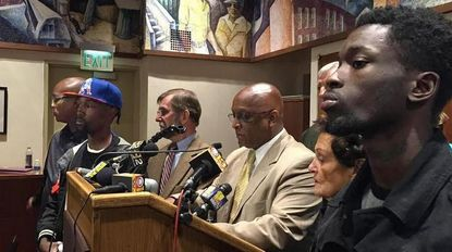 Self-described gang members stand with members of the Baltimore City Council to condemn rioting.