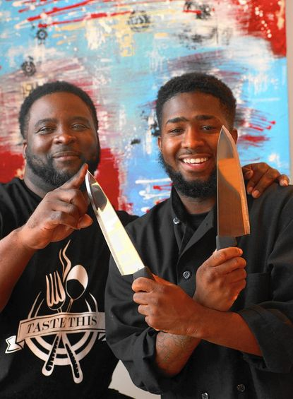 Taste This -- chef/owners. Dante Davis (left) tests a knife held by Craig Curbean (right) as the two prepare for opening day of their new eatery at the corner of 25th and St. Paul streets. The space is decorated with original paintings by Curbean. (The art in the background, that is).
