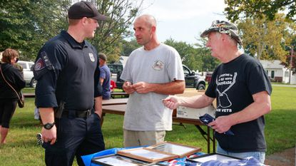 County Police Officer Cpl. Matt Sanchez (left) gives Michael Vaccarino (center) an Anne Arundel County K-9 Unit Challenge Coin during Riviera Beach Appreciation Day. Larry Drymon (right) has been helping with appreciation day honoring military and first responders for two years.