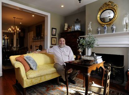 Dr. John Hawkins sits in the front parlor of his dream home in the Federal Hill neighborhood.