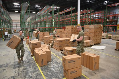 Members of the Maryland Air National Guard 175th Logistics Readiness Squadron work with members of the Maryland Office of Preparedness and Response to prepare and load medical supplies and equipment at the Maryland Strategic National Stockpile location.