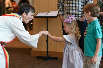 Rev. Paige Getty welcomes Lillian Hines, 3, of Ellicott City to a gathering at the Unitarian Universalist Congregation of Columbia.